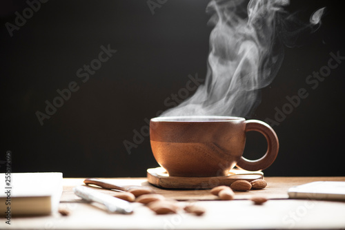 Stickers pour portes The Hot tea with steam in wood cup and almonds on the wooden table black background.