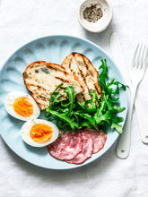 Delicious Breakfast Or Snack - Salami Sausage, Boiled Egg, Arugula, Grilled Bread And Coffee On A Light Background, Top View