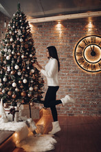 Side View Full Length Of Slim Young Girl With Long Dark Hair In White Sweater, Black Leggings And White Socks Decorating Christmas Tree At Home . Clock On Brick Wall Shows Almost Midnight.