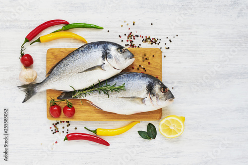 Fotografie, Obraz  Raw fresh dorada fish with spices on wooden cutting board