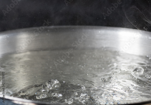 Fotografija  Boiling water in a metal pan close-up