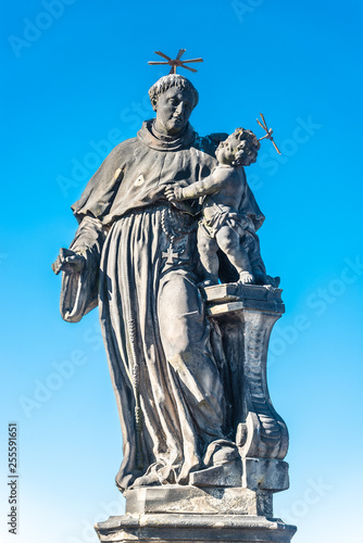 Foto  Statue of fat and big priest with a child at the Charles Bridge in Prague at blu