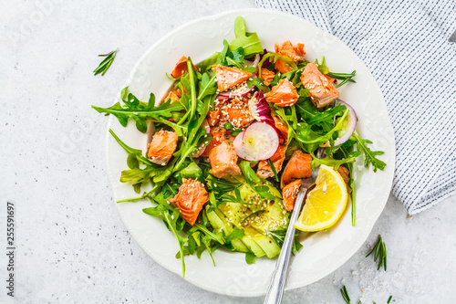 Photo Baked red fish salad with avocado, cucumber, radish and arugula in white plate, top view