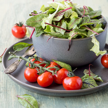 Fresh Green Salad Mix In A Bowl And Small Red Tomatoes On A Round Plate On The Wooden Table. Selective Focus.