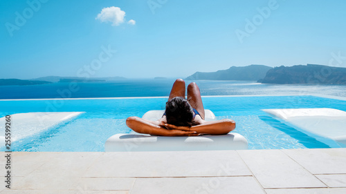 Fototapeta Young woman on vacation at Santorini, women at the swimming pool looking out over the Caldera ocean of Santorini, Girl at the infinity pool Oia Santorini Greece obraz