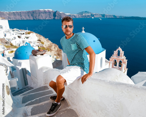 Fototapeta Santorini greece, young middle age men on vacation in Santorini Greece, man at the village of Oia with white house and blue church roofs obraz