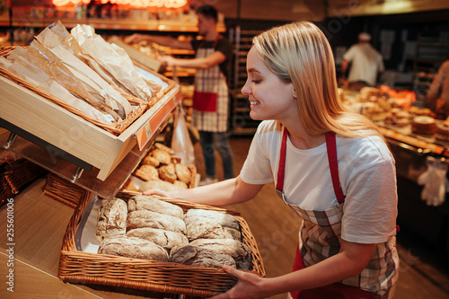 Young woman hold bakset with fresh bread in grocery store. She put it on shelf and smile. Tasty and delisious. Working inside. Warm light.