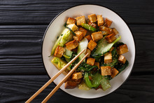 Stir Fry Tofu With Bok Choy And Sesame Seeds Close-up On A Plate. Horizontal Top View