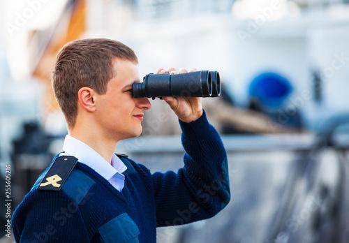 Photo boatswain with binoculars near the boat.