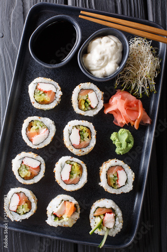 Fototapeta set of Japanese rolls uramaki served with sauces, ginger and wasabi closeup on the table. Vertical top view obraz