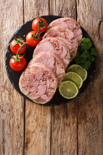 Papel de parede Delicious sliced Head cheese or brawn served with tomatoes, lime and cilantro closeup on a slate board