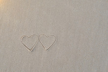 Two Heart Shapes Written In The Sand On The Beach Morning Sunlight.