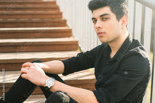 Fotografia  Portrait of a handsome young successful male brunette of a Turkish Mediterranean race sitting on the urban stairs in a black shirt and jeans