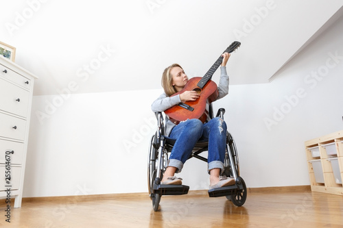 Vászonkép  Disabled young woman in wheelchair playing the guitar.