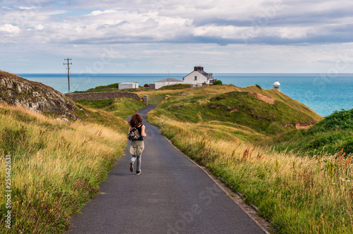 Happy young Caucasian female tourist running on an empty road towards the Baily lighthouse on Howth Head, Dublin, Ireland Canvas Print
