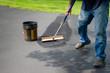 canvas print picture - Homeowner spreads blacktop asphalt sealant on driveway