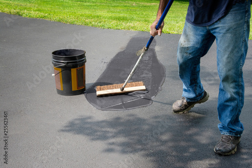 Photo Homeowner spreads blacktop asphalt sealant on driveway
