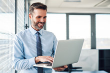 Handsome Businessman In Modern Office Looking On Laptop