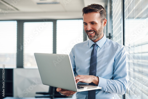 Photographie  Businessman in modern office working on laptop