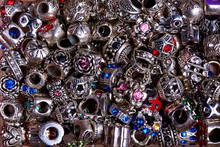 Silver Beads Of Different Shapes With Colored Stones Close-up.