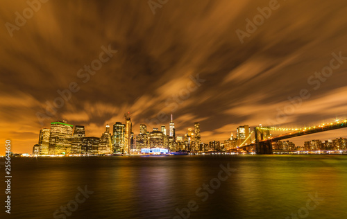 Manhattan panoramic skyline at night with Brooklyn Bridge. New York City, USA. Office buildings and skyscrapers at Lower Manhattan (Downtown Manhattan).