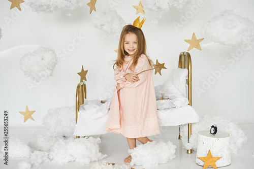 Fotografie, Obraz  Little princess with a magic wand on а bed in a cloud on a white background
