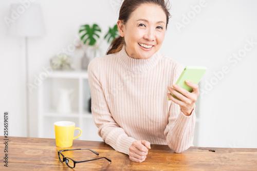 Foto  スマートフォンを見るシニア女性