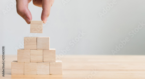 Photo Hand arranging wood block stacking as step stair