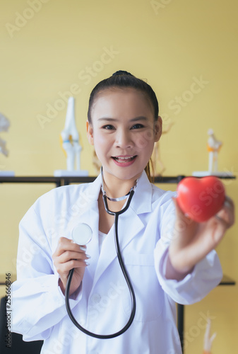 Fotografie, Obraz  Doctor asian female hands holding stethoscope and heart red model,Happy and smil
