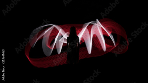 Photo  Woman silhouette against red and white backlight in shape of wings