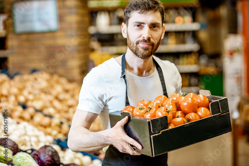 Portrait of a handsome shop worker or farmer holding box with fresh tomatoes in the vegetable department in the supermarket