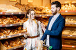 Young and happy couple choosing fresh pastries, standing together with shopping cart in the bakery department of the supermarket