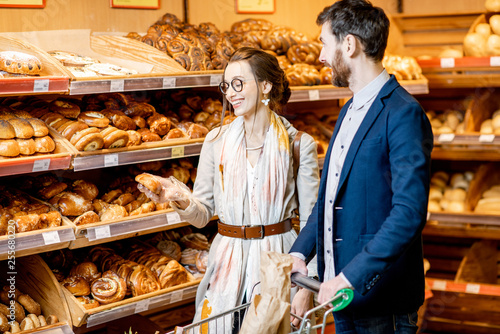 Deurstickers Bakkerij Young and happy couple choosing fresh pastries, standing together with shopping cart in the bakery department of the supermarket