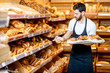 Handsome baker in uniform putting fresh pastries on the shelves in the supermarket