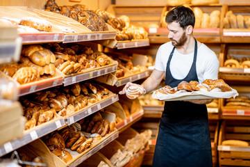 Zgodan pekar u odori stavlja svježe pecivo na police u supermarketu