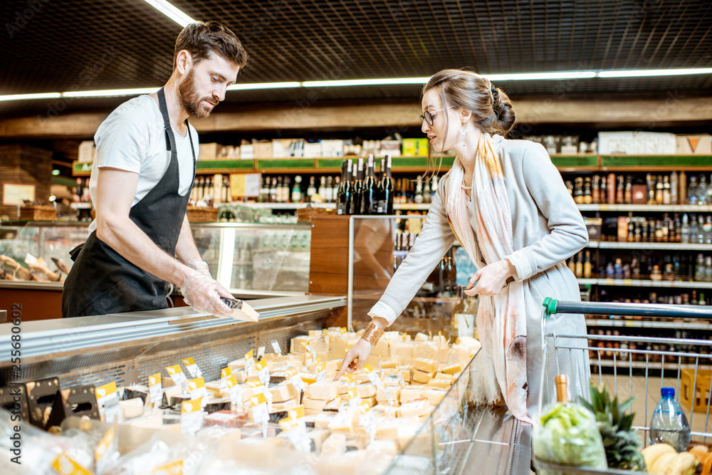 Fototapety, obrazy: Handsome seller choosing cheese for a young woman client in the supermarket