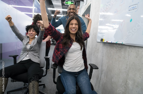 Fototapety, obrazy: multiethnics business team racing on office chairs