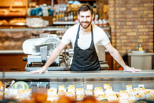 Portrait of a handsome seller or shop worker in apron standing at the counter in the supermarket