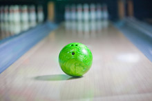 Green Bowling Ball Put On Alley With Blurred Bowling Pin Background