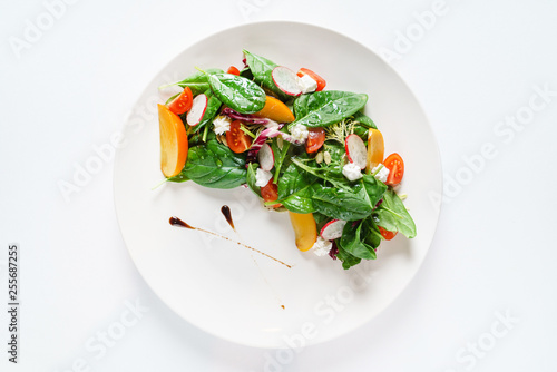Fototapeta salad with spinach and persimmon on the white plate obraz