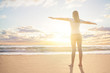 Happy young woman traveller enjoys her summer vacation in a morning sun dawn on a tropical beach resert