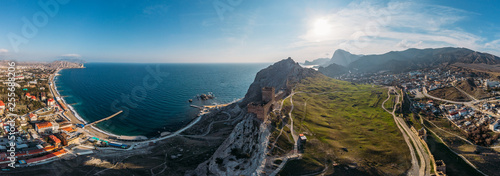 Genoese fortress in Sudak, Crimea. Aerial panorama view of ruins of ancient historic castle on crest of mountain near sea and small town at foot of rocks. Beautiful summer tourist landscape #255688206
