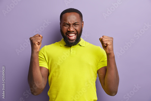 Fotografía  Emotional black ethnic man raises fists with cheer, laughs happily, shows white teeth, shouts for favourite football team, dressed in casual clothes, models over purple background