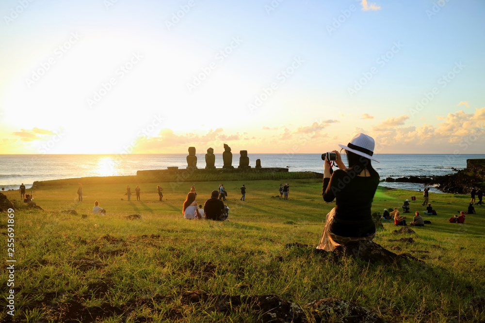 Fototapety, obrazy: Female Tourist Taking Photos of the Famous Sunset Scene at Ahu Tahai, Easter Island, Chile