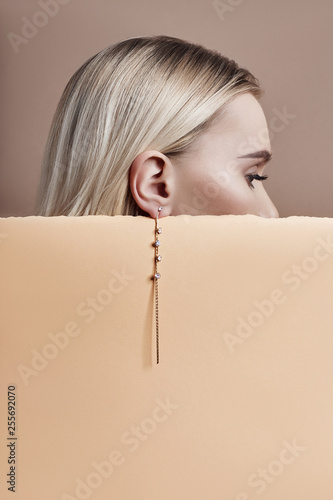 Valokuva Earrings and jewelry in ear of a sexy blonde woman pressed against the paper beige