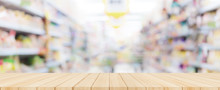 Wooden Table Top With Blurred Supermarket In Background, Panoramic Banner.
