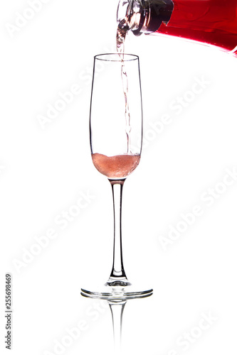 Fotografia  pouring pink wine into glass, isolated on white background
