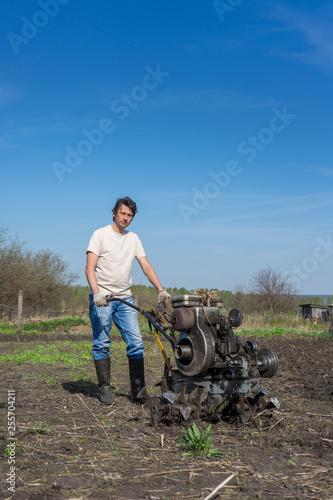 In de dag Afrika Man with cultivator ploughs ground. Land cultivation, soil tillage. Spring work in the garden. Gardening concept