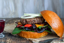 Venison Burger In Brioche Bun With Peppery Leaf Salad, Onion, Roast Peppers And Lingonberry Sauce