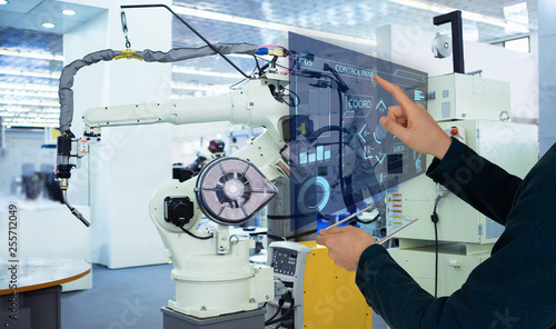 Pinturas sobre lienzo  The engineer uses a futuristic projection touch screen to control robots in a smart factory